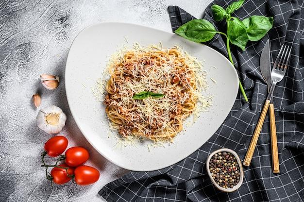 Spahgetti tradizionali italiani alla bolognese, alla bolognese, pasta. basilico, carne macinata, pomodori. sfondo grigio. vista dall'alto