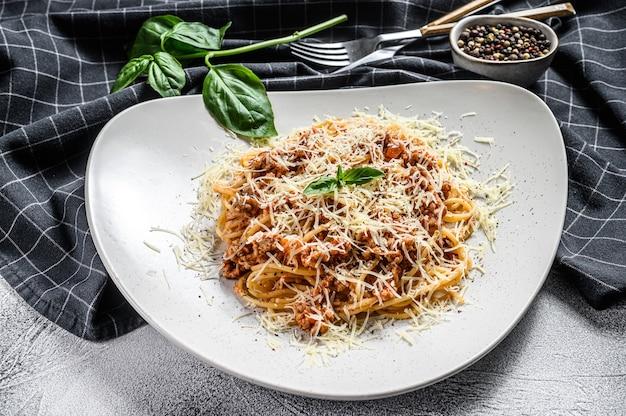 Spahgetti italiani tradizionali alla bolognese, bolognese, tagliatelle di pasta. basilico, carne macinata di manzo, pomodori