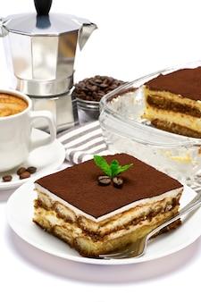 Dessert di tiramisù italiano tradizionale nella porzione di teglia di vetro sul piatto e tazza di caffè isolato su bianco
