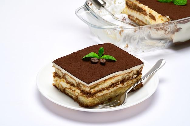 Dessert di tiramisù italiano tradizionale nella porzione di piatto di cottura di vetro sul piatto e sulla scapola isolata su bianco