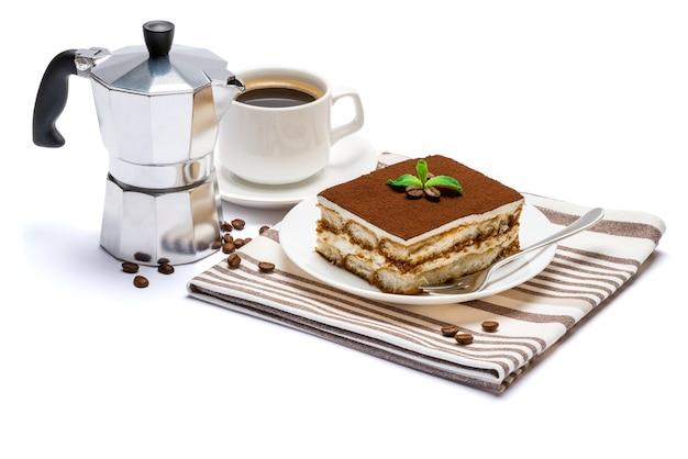 Porzione quadrata del dessert tiramisù italiano tradizionale sul piatto in ceramica, caffettiera moka e tazza di caffè espresso fresco isolato