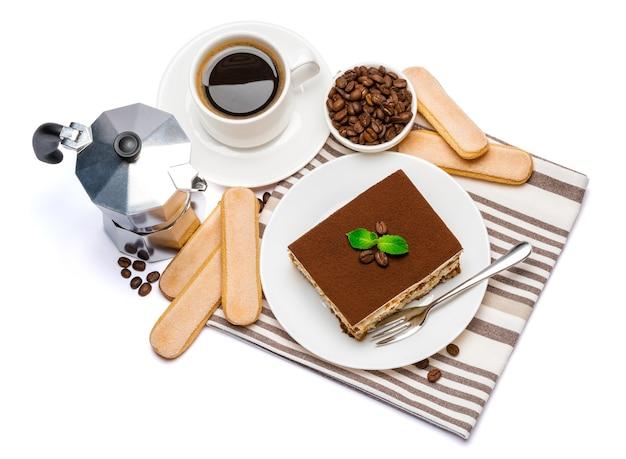 Porzione quadrata di dessert tiramisù italiano tradizionale sul piatto in ceramica, caffettiera moka, biscotti savoiardi e tazza di caffè espresso fresco isolato