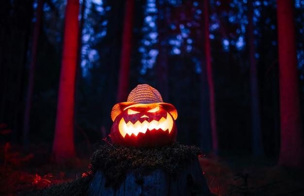 Lanterna tradizionale della testa dei jack per halloween sullo sfondo di un cupo concetto di foresta rossa di hor...