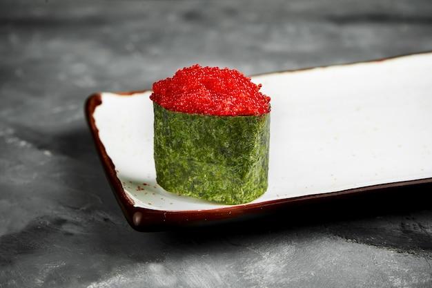 Sushi gunkan giapponese tradizionale con caviale tobiko e salsa piccante in nori su un piatto bianco. primo piano, messa a fuoco selettiva