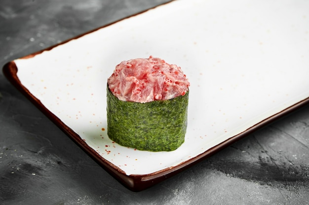 Sushi gunkan giapponese tradizionale con tonno, caviale e salsa piccante in nori su un piatto bianco. primo piano, messa a fuoco selettiva