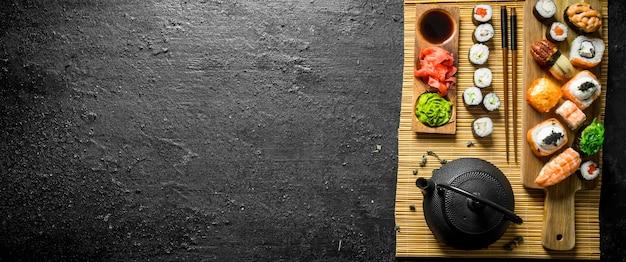 Sushi, maki e panini giapponesi tradizionali su un tovagliolo. sulla tavola rustica