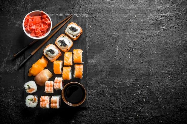 Rotoli di sushi tradizionali giapponesi con zenzero e salsa di soia su una tavola di pietra nera. sulla tavola rustica nera