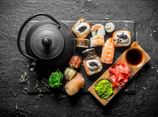 Rotoli di sushi giapponesi tradizionali con tè verde. su sfondo nero rustico