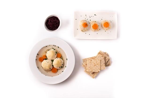 Zuppa di palla di matzah ebraica tradizionale, pesce gefilte e pane di matzah isolato su sfondo bianco