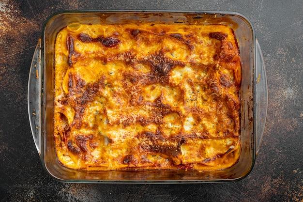 Lasagna tradizionale a base di ragù alla bolognese di manzo macinata condita con foglie di basilico set, in teglia