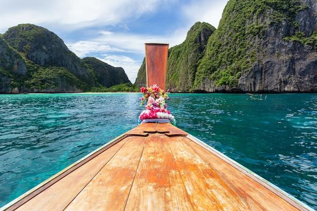 Barca tradizionale longtail con una splendida vista del paesaggio a maya bay sull'isola di phi phi leh nella giornata di sole