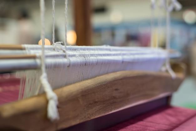 Lo stile vintage della macchina a telaio tradizionale è lo strumento per tessere la seta tailandese dal bozzolo