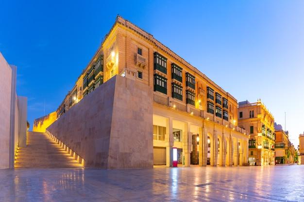 La tradizionale strada maltese, le scale e l'edificio con balconi colorati vicino alla porta della città di la valletta nel centro storico di la valletta, capitale di malta