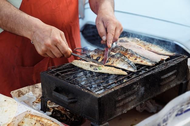 Cucina tradizionale mediterranea. l'uomo sta grigliando il pesce bianco balyk al mercato di strada, primo piano delle mani. gira il pesce e stacca la squama. cibo di strada locale in turchia.
