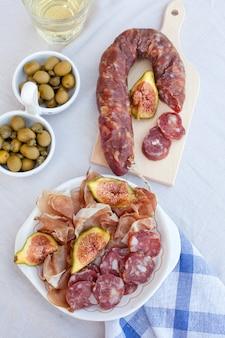 Antipasti di carne mediterranei tradizionali con olive, fichi e vino bianco