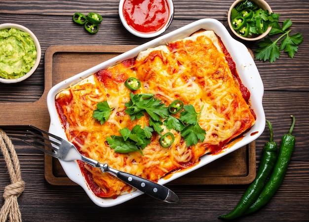 Enchiladas piatto messicano tradizionale con carne, salsa di peperoncino rosso e formaggio in una casseruola bianca su fondo di legno rustico, servito con guacamole e salse di pomodoro. primo piano, vista dall'alto