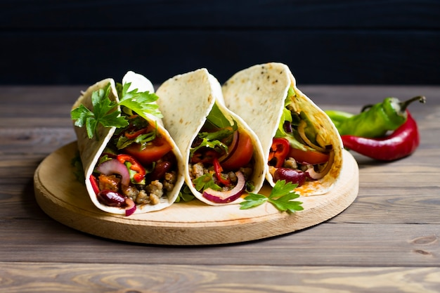 Tacos messicani tradizionali con carne e verdure. su una tavola di legno.