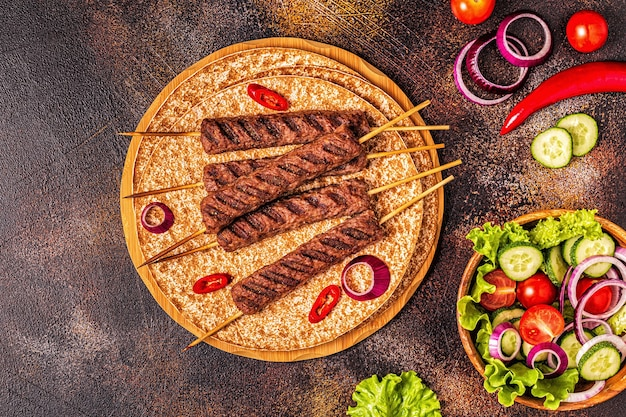 Spiedino di carne tradizionale medio orientale arabo o mediterraneo con verdure e pane lavash