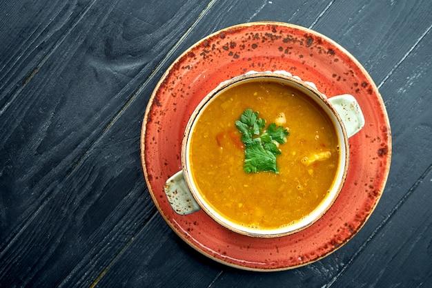 Zuppa tradizionale marocchina - harira, zuppa di lenticchie gialle con coriandolo in un piatto rosso su una superficie di legno nero. zuppa dietetica