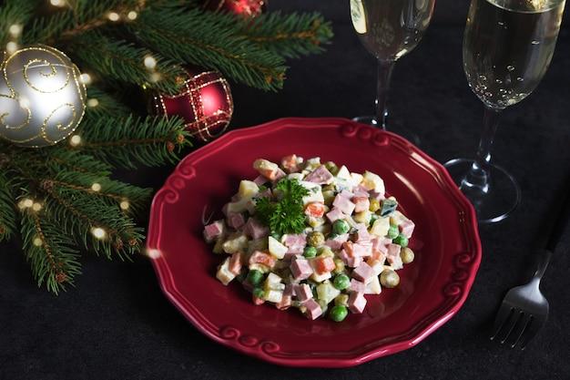 Insalata tradizionale di capodanno olivier. tavola festiva di capodanno e bicchieri di champagne.