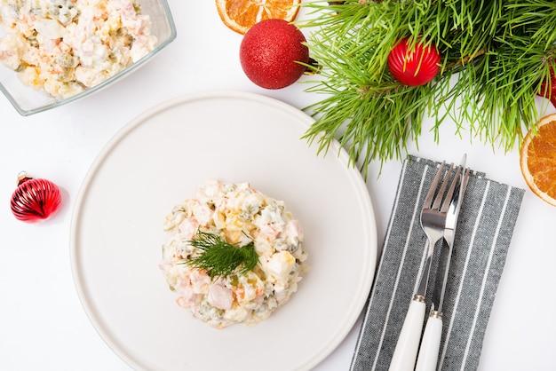 Olivier di insalata di capodanno tradizionale con decorazioni festive su sfondo bianco, vista dall'alto