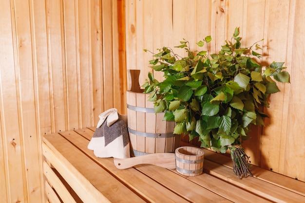 Vecchio concetto russo tradizionale della stazione termale dello stabilimento balneare. dettagli interni sauna finlandese bagno di vapore con accessori per sauna tradizionale bacino di betulla scopa paletta in feltro. rilassati il concetto di bagno del villaggio di campagna.