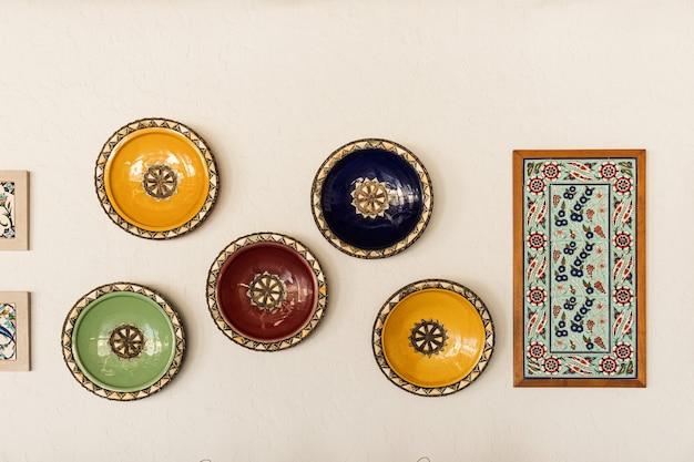 Decorazioni di design d'interni da bar tradizionale orientale. piatti ornamentali colorati su parete bianca