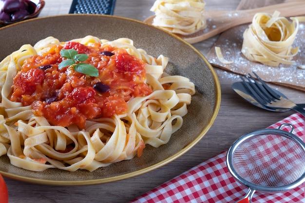 Spaghetti di tagliatelle di pasta tradizionale sul tavolo.