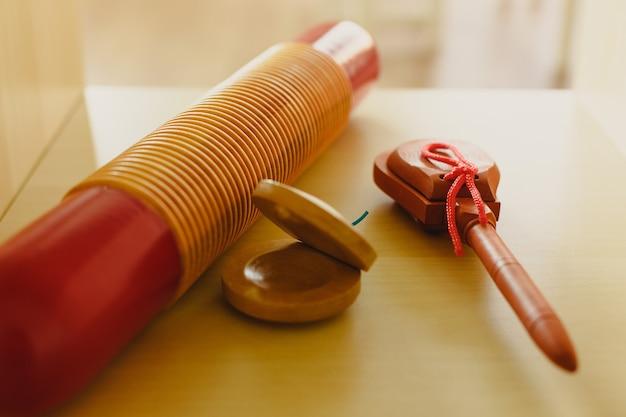 Strumenti musicali tradizionali a percussione, come nacchere e scatole di legno cinesi.