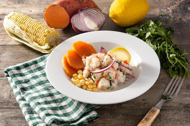 Ceviche peruviano tradizionale con pesce, patate dolci, mais e verdure sulla tavola di legno