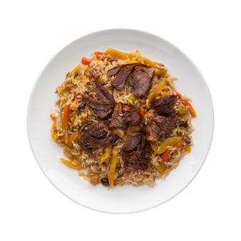 Pilaf tradizionale con carne in un piatto su sfondo bianco. vista dall'alto. isolato