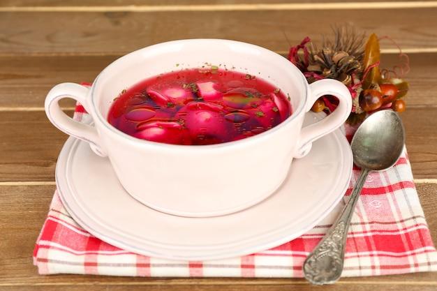 Borscht rosso chiaro polacco tradizionale con gli gnocchi in ciotola sul vassoio e le decorazioni di natale su fondo di legno