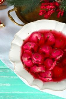 Borscht rosso chiaro polacco tradizionale con gnocchi e decorazioni natalizie su sfondo di tavolo in legno colorato