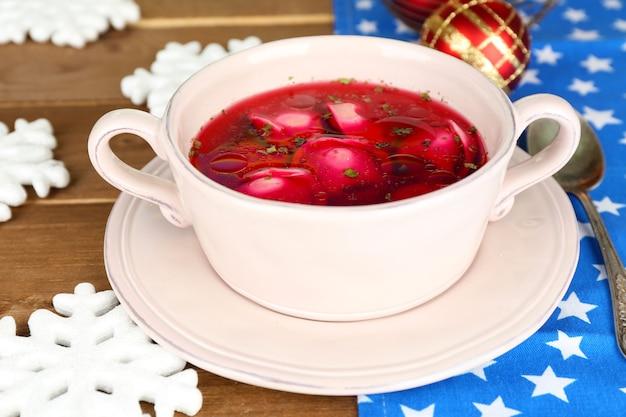 Borscht rosso chiaro polacco tradizionale con gnocchi e decorazioni natalizie su fondo di legno