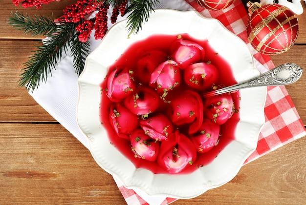 Borscht rosso chiaro polacco tradizionale con gli gnocchi e le decorazioni di natale sul fondo di legno della tavola