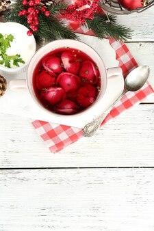 Borscht rosso chiaro polacco tradizionale con gnocchi e decorazioni natalizie su tavola di legno wooden