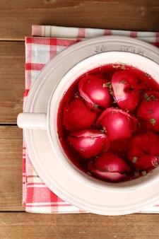 Borscht rosso chiaro polacco tradizionale con gnocchi su fondo di legno wooden