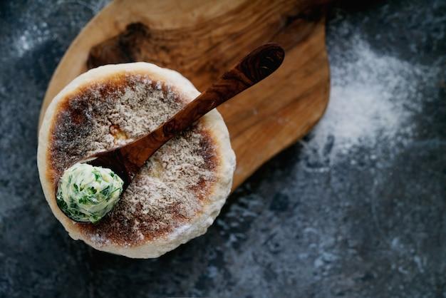 Pane circolare piatto tradizionale portoghese bolo do caco. cucchiaio di burro all'aglio con verdure in cima. vista dall'alto