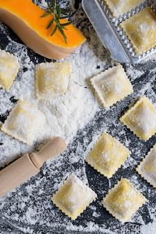 Ravioli crudi tradizionali con la zucca su una tavola di legno con farina, fatta a mano, processo di cottura