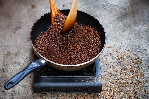 Torrefazione tradizionale del caffè a casa, chicchi di caffè appena tostati.