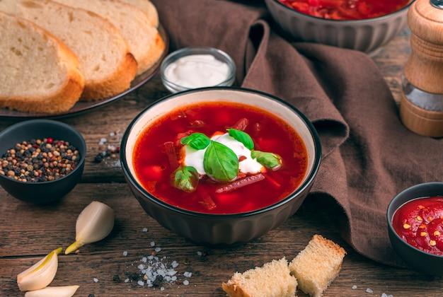 Borscht russo tradizionale con barbabietola rossa su uno sfondo di aglio, pane e spezie. il concetto di sfondi culinari.