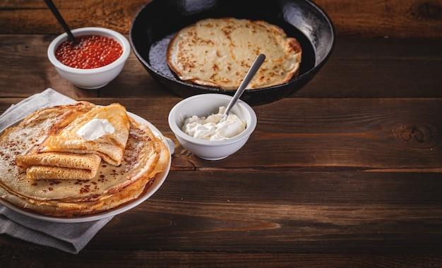 Crepes russe tradizionali blini impilati nel piatto e padella in ghisa con caviale rosso, panna acida fresca sul tavolo di legno scuro. pasto del festival russo maslenitsa o shrovetide. spazio per il testo