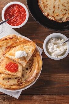 Crepes russe tradizionali blini impilati nel piatto e padella in ghisa con caviale rosso, panna acida fresca sul tavolo di legno scuro. pasto del festival russo maslenitsa o shrovetide. vista dall'alto.