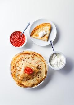 Crepes russe tradizionali blini impilati in un piatto con caviale rosso, panna acida fresca. pasto tradizionale festa russa di maslenitsa. cibo russo, cucina russa. vista dall'alto.