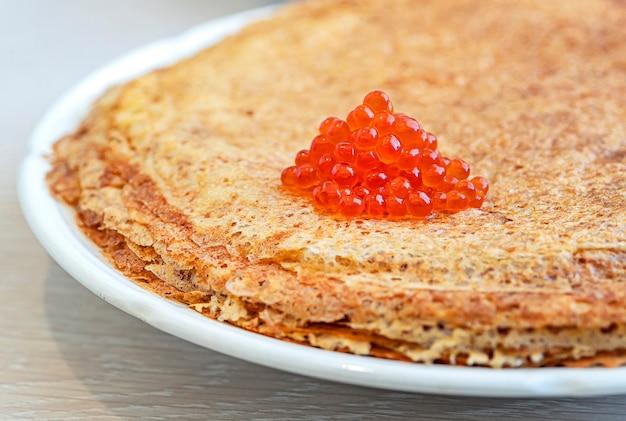 Pancake russi tradizionali con caviale rosso su piatto bianco su un tavolo di legno