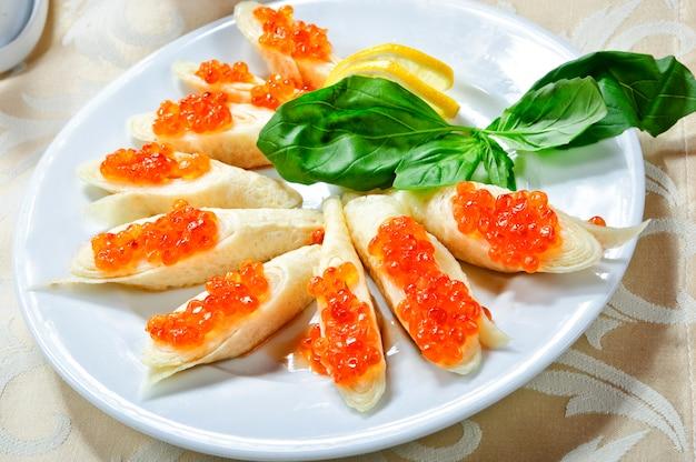 Pancake russi tradizionali con caviale rosso.