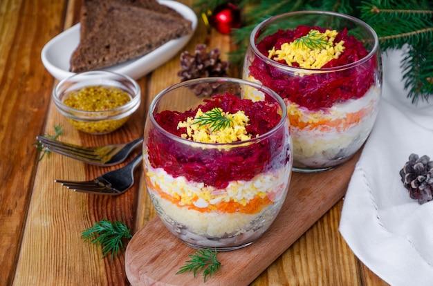 Aringhe russe tradizionali dell'insalata sotto una pelliccia in un vetro