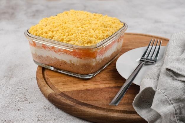 Insalata russa tradizionale mimosa con verdure e pesce. insalata a strati con patate, tonno, carota, cipolla, uova e maionese.