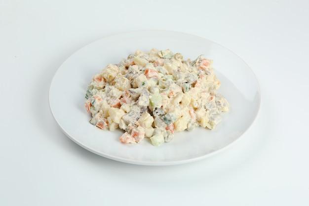 Insalata russa tradizionale olivier di verdure bollite e carne con salsa in una ciotola. capodanno russo o natale isolato su bianco.