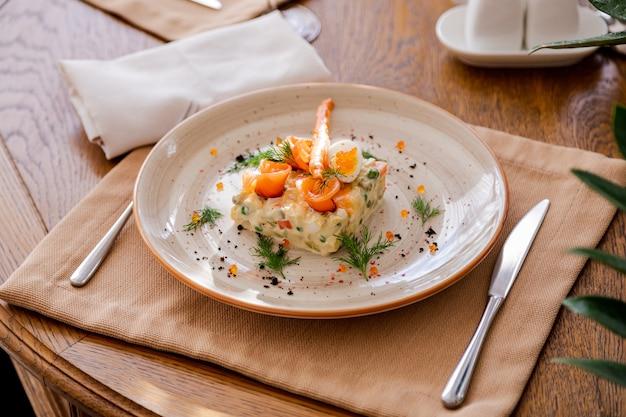 Insalata russa tradizionale olivier. l'insalata è decorata con salmone e uova di quaglia.